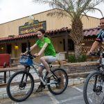 A couple enjoy a bike ride through Furnace Creek.