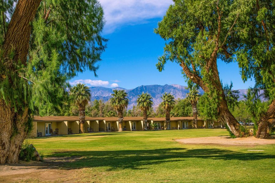 The main lawn of the Ranch at Furnace Creek is surrounded by lush vegetation.