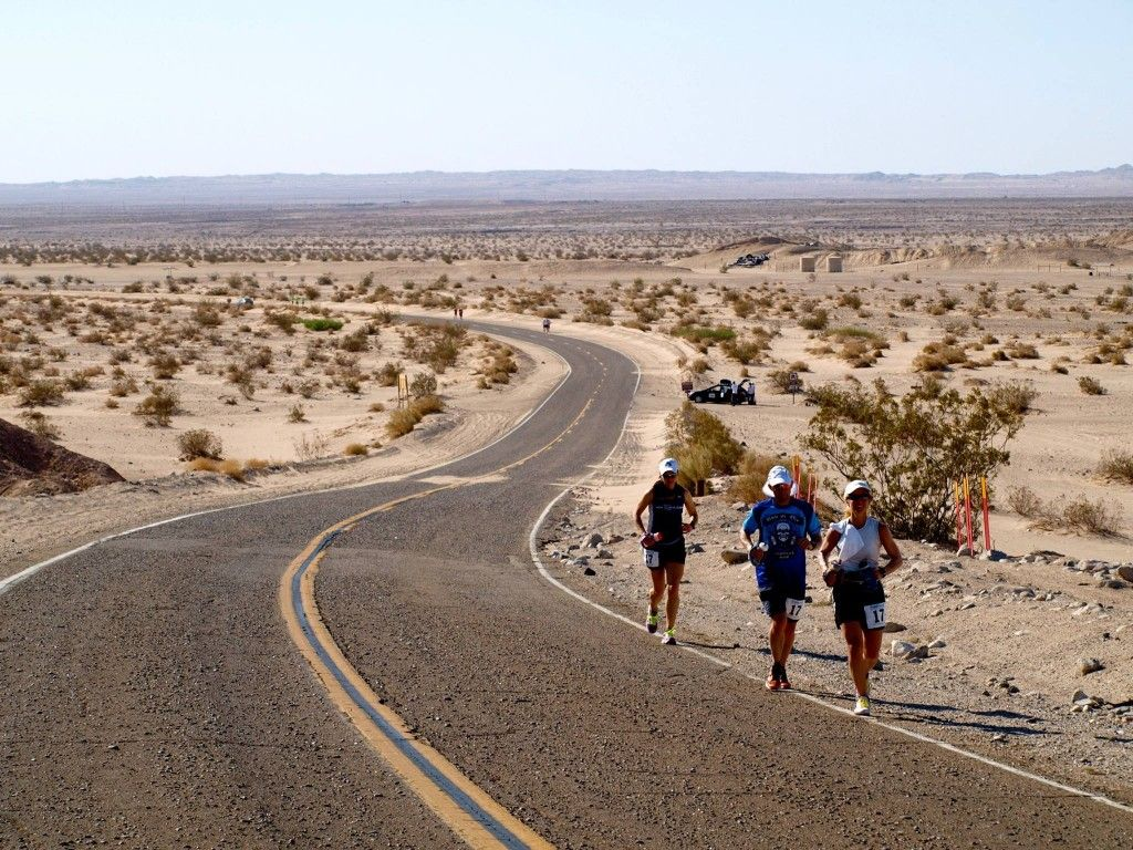 A group of runners jog through a desolate desert landscape.