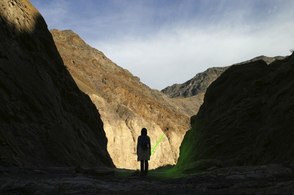 A silhouette of a person standing in Death Valley, holding a green light saber.