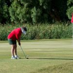A woman tees up as her partner looks on at the Furnace Creek Golf Course.