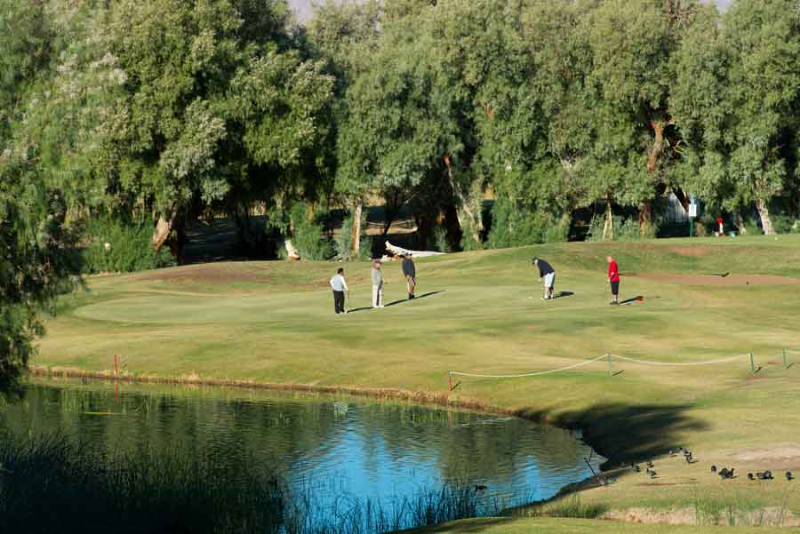 A group of golfers next to a water hazard at the Furnace Creek Golf Course.