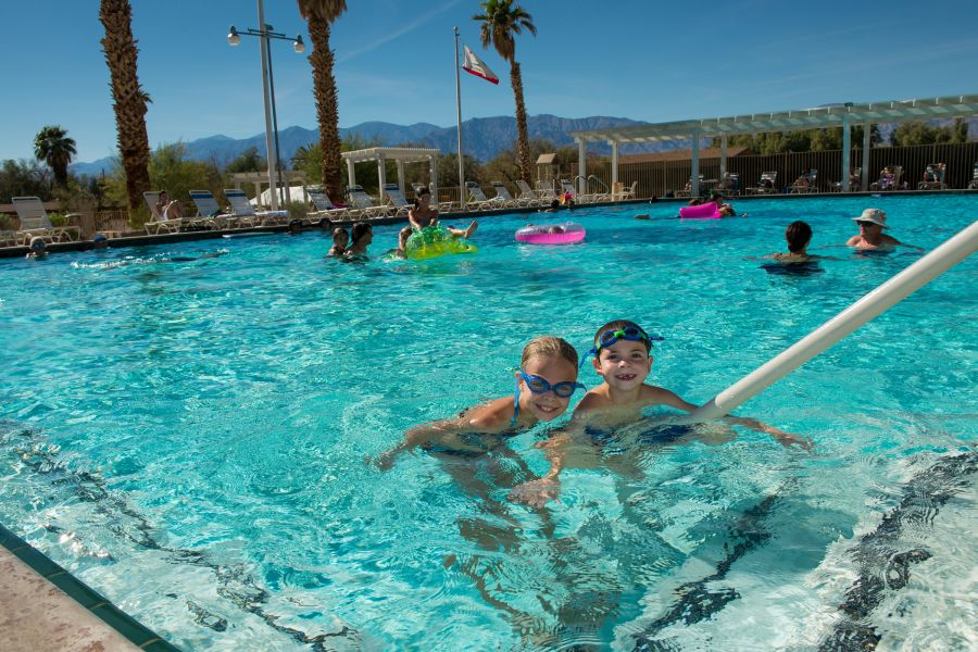 Happy children play in a swimming pool under a sunny sky.